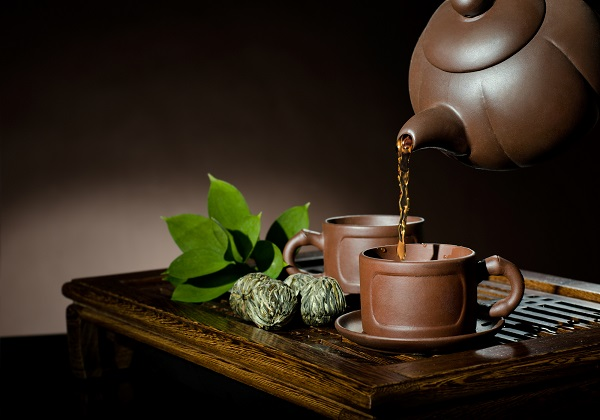 horizontal photo, of the clay teapot tea flow in  cup on brown background,  tea ceremony
