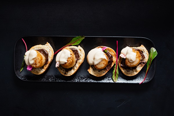 scallop appetizers with sauce on the black background